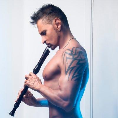 El flautista Horacio Franco en un retrato con el dorso desnudo mientras toca la flauta