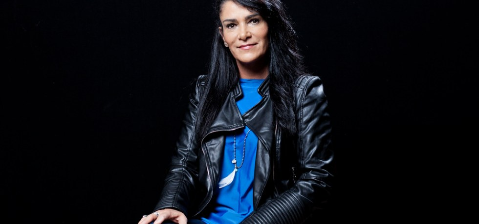 La periodista Lydia Cacho posa de frente con una blusa azul y una chamara de piel