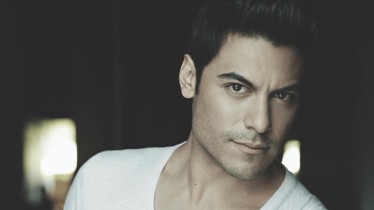 Retrato del cantante Carlos Rivera donde mira a cámara usando una camiseta blanca.